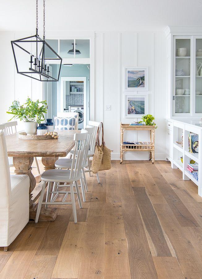 Lake house dining space, rattan bar cart, coastal art