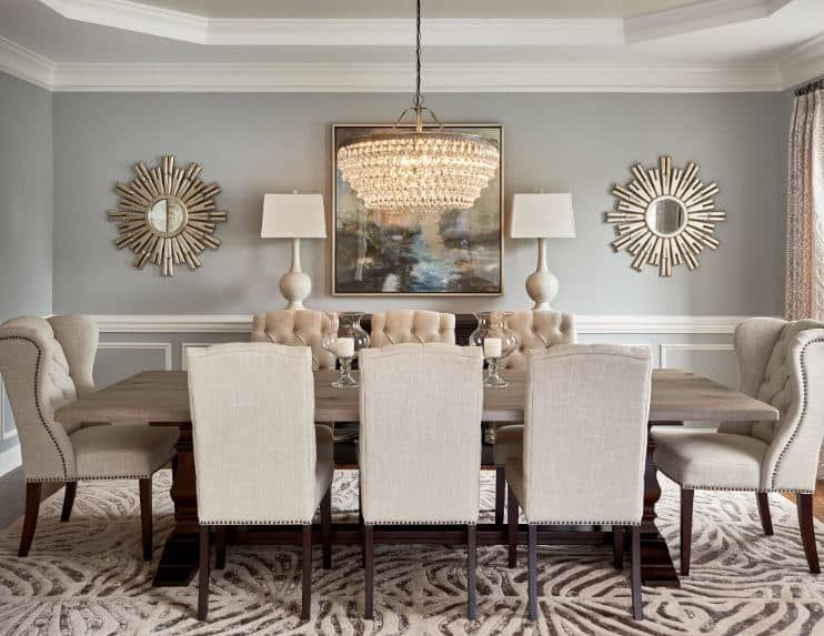 The light gray walls of this formal dining room is adorned with a colorful painting that is flanked by table lamps and a couple of sun-shaped mirrors that pair well…