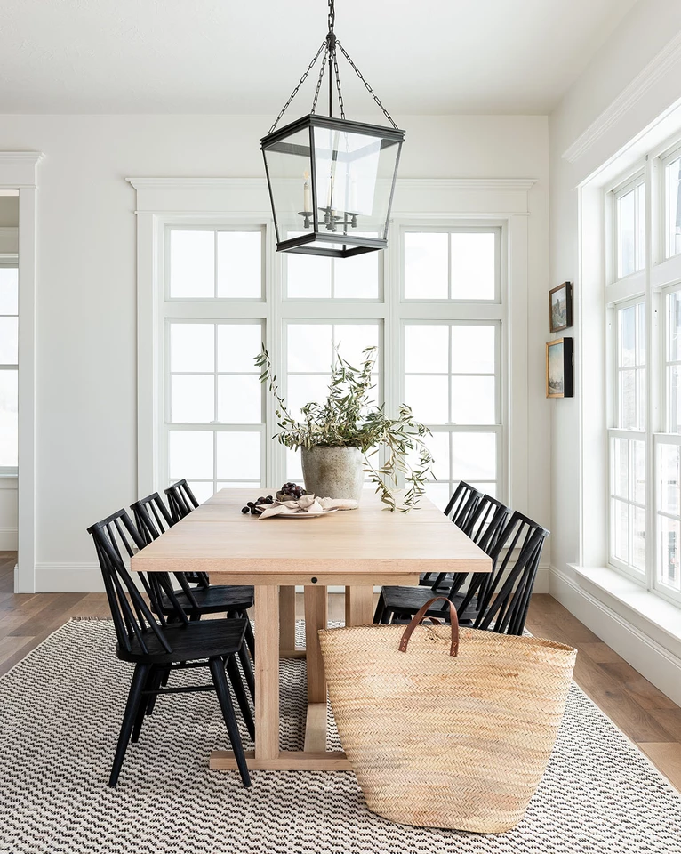 similar table, natural wood, with black chairs. Pattered rug, Brass light fixture similar style.